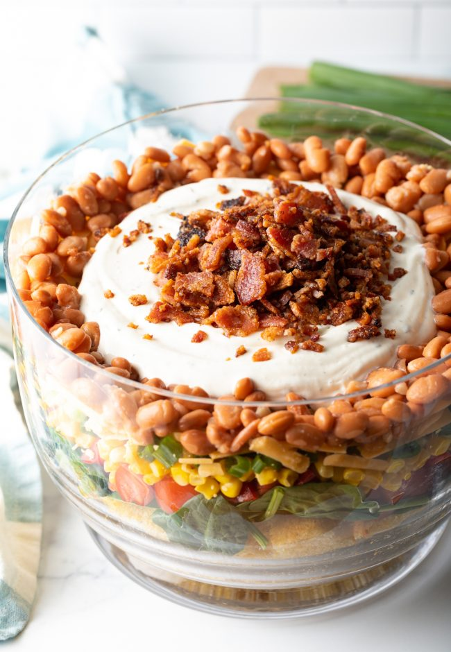 side view of cornbread salad with layers of goodies all topped with dressing and bacon