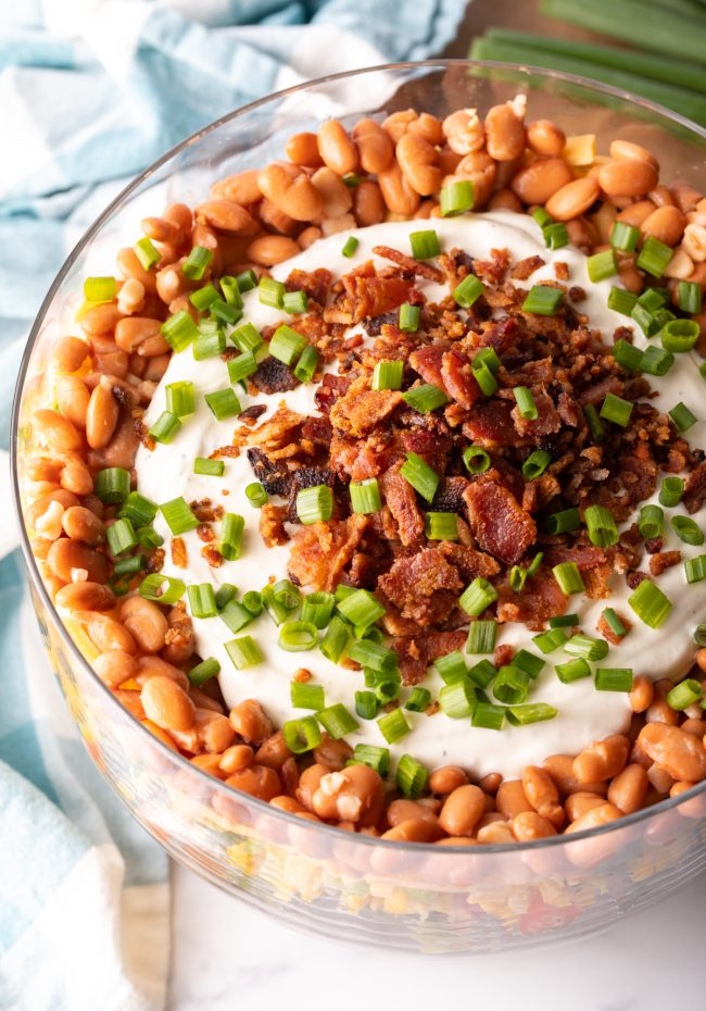 overhead view of layered cornbread salad topped with beans, ranch dressing, bacon and scallions