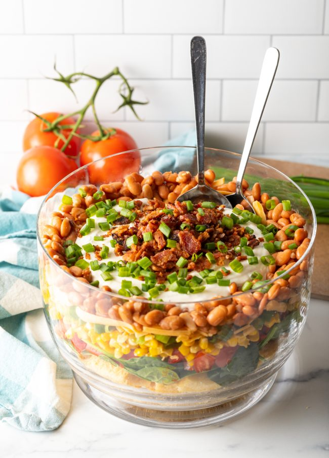 view of complete layered southern retro cornbread salad with two large spoons