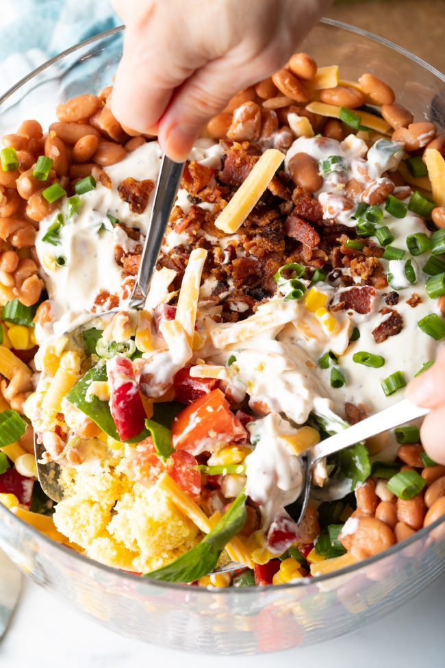 two spoons scooping salad with cubes of corn bread, veggies, cheese, and ranch dressing