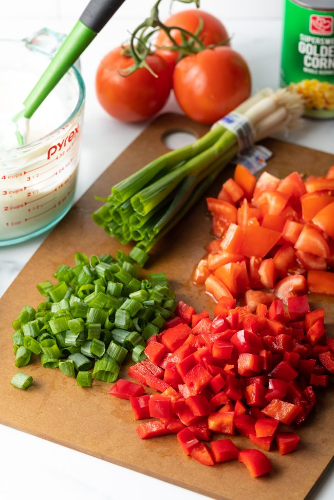 chopped tomatoes, peppers, scallions on a cutting board
