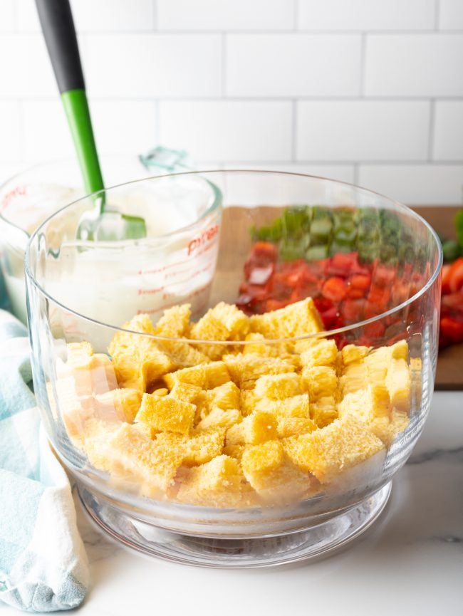 glass container with a layer of cubed cornbread