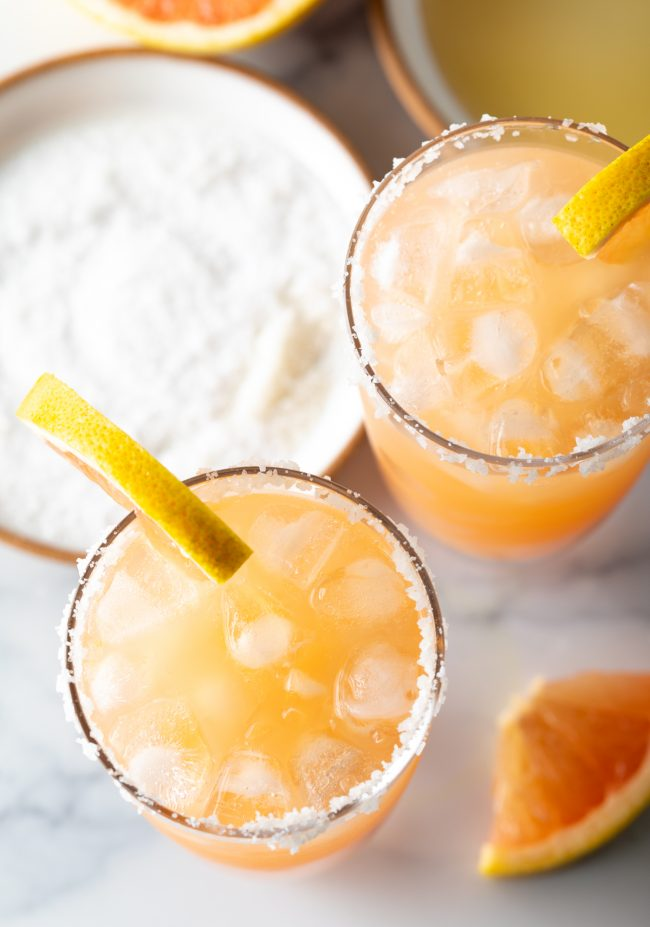overhead view of two glasses of vodka drinks garnished with salt and grapefruit slices