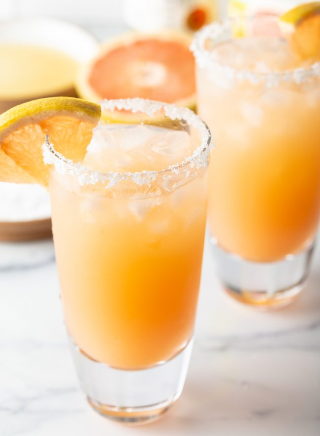 two glasses of salty dog drinks with grapefruit garnishes