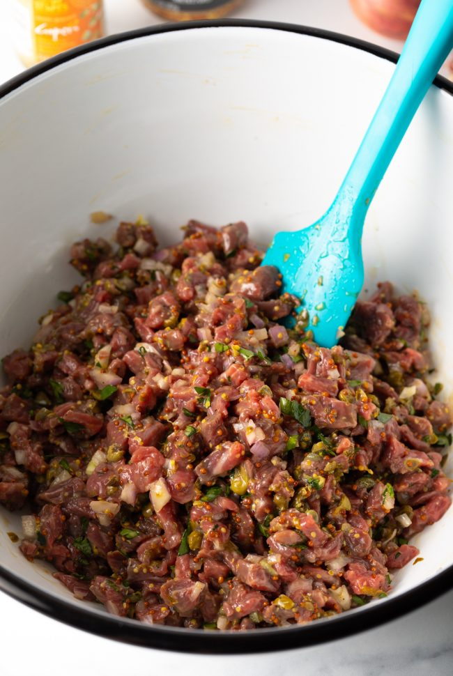 mixing bowl with chopped beef, mustard, onions, capers, egg yolk, and seasonings to make the steak tartare recipe