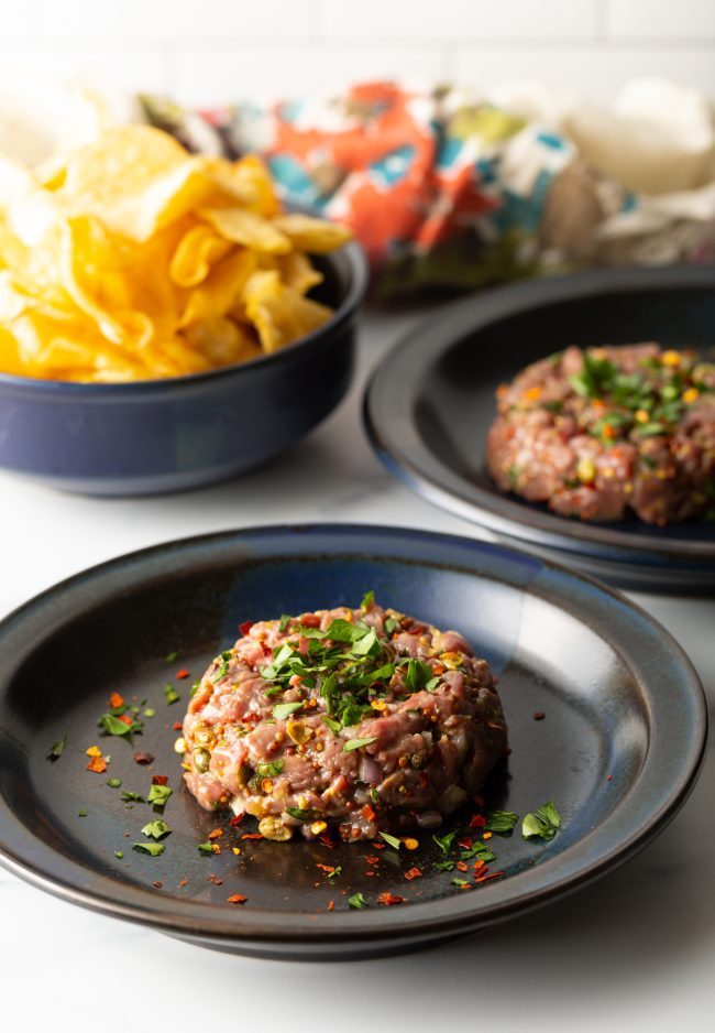 two portions of beef tartare on plates