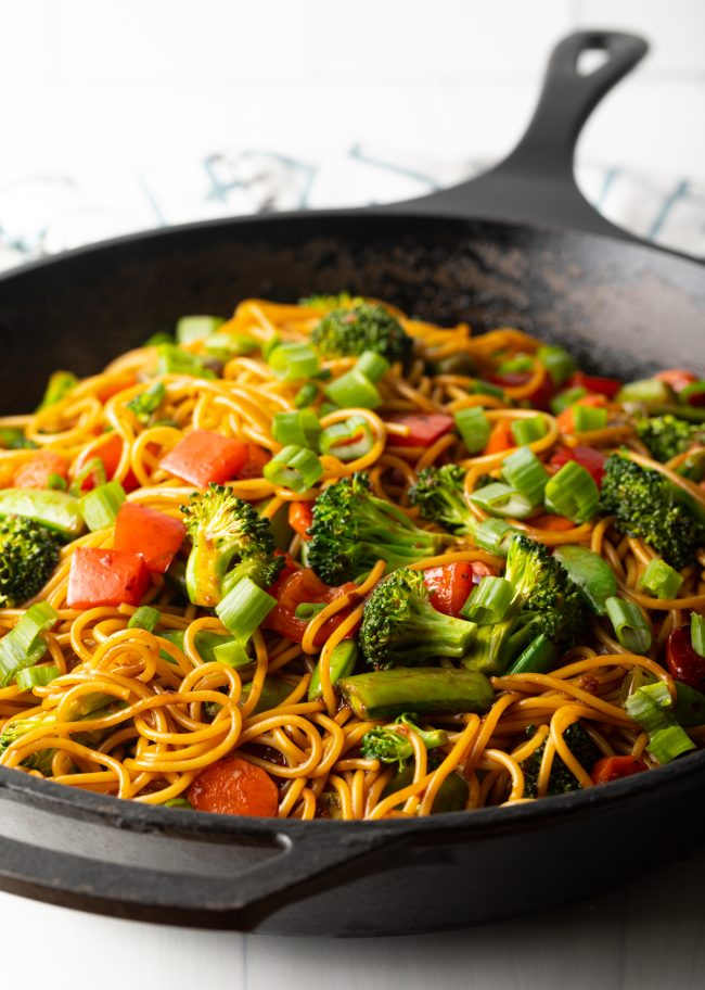 side view of homemade vegan stir fry sauce with vegetables and noodles in a skillet