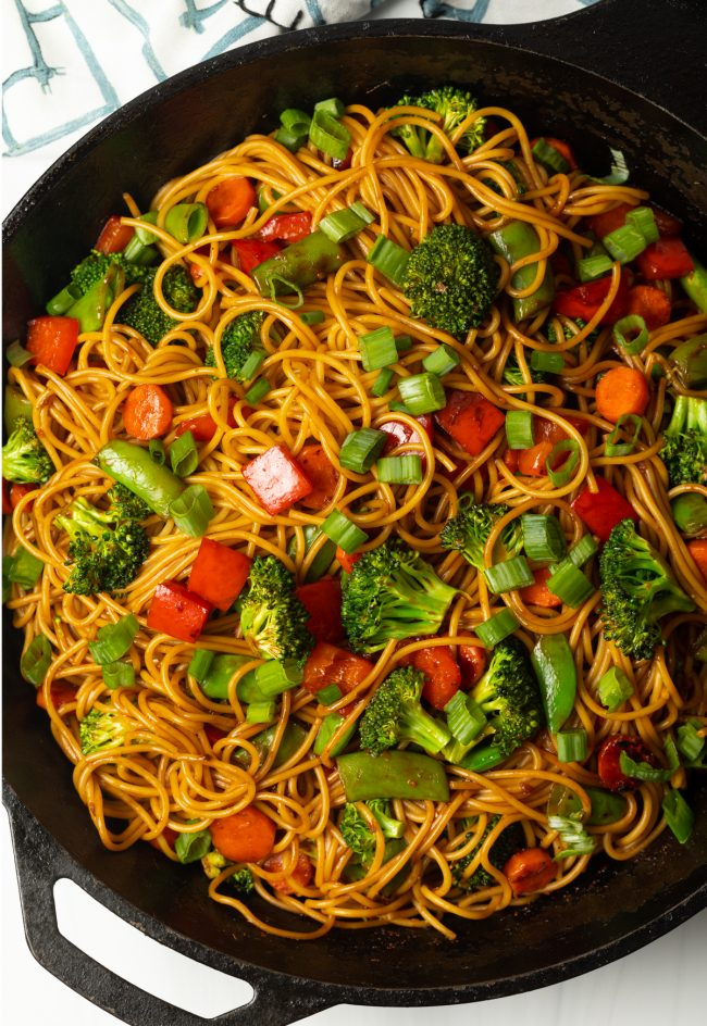 overhead view of stir fry vegetables and noodles with vegan sauce