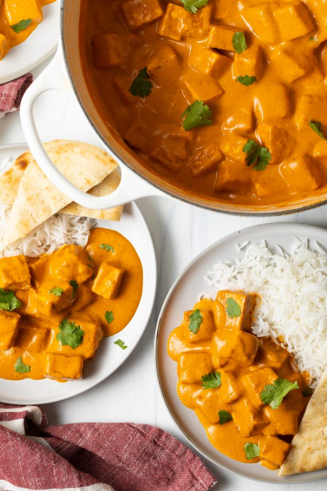 overhead view of pot with paneer tikka masala, two bowls with rice and paneer