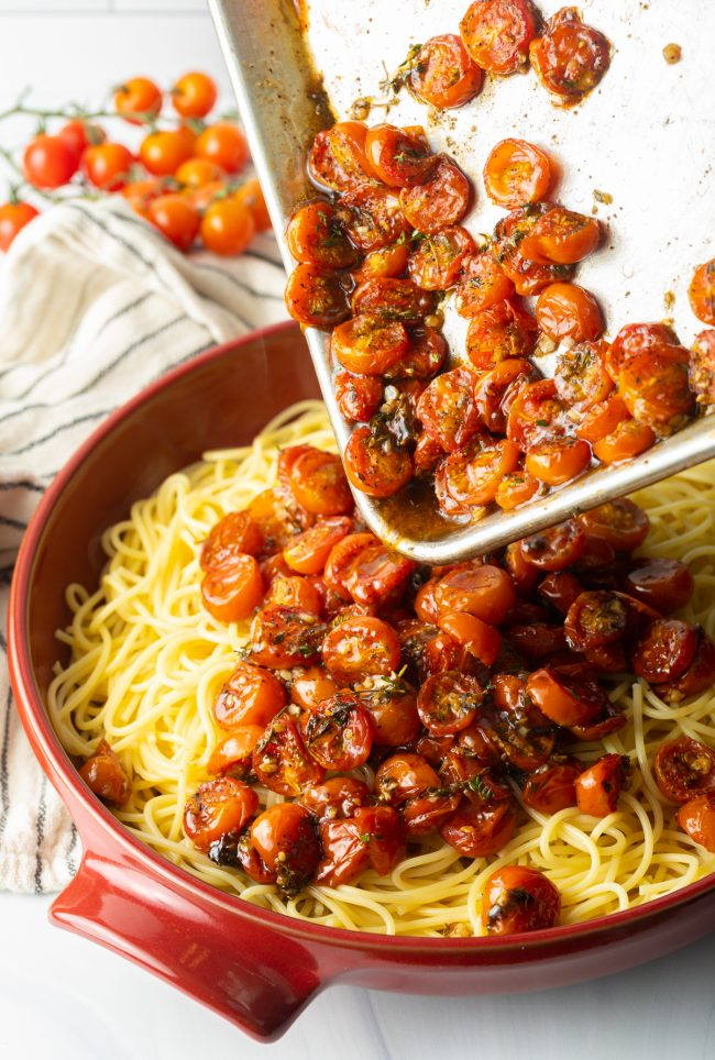 pouring balsamic roasted tomatoes into bowl of pasta