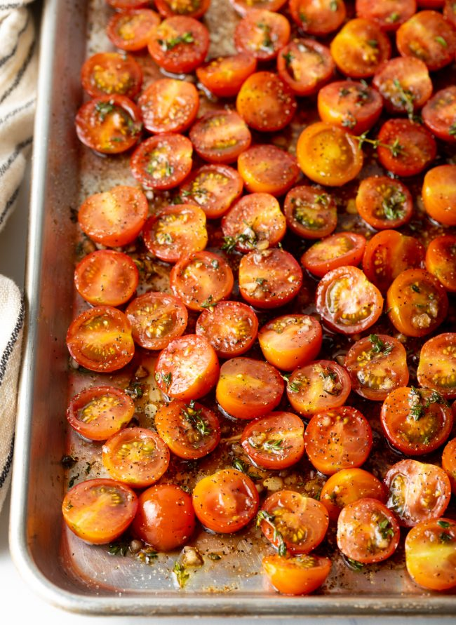 coated tomatoes in vinegar, garlic, and herbs on a baking sheet