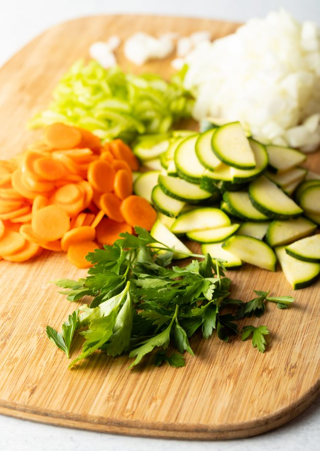 cutting board with carrots, zucchini, onion, celery