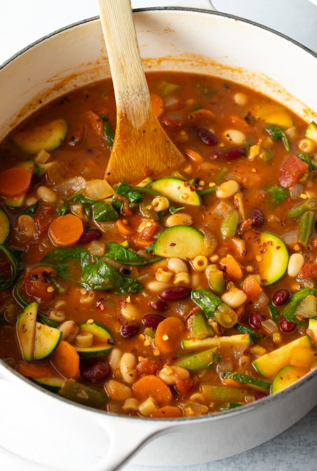 overhead side view of homemade minestrone soup with vegetables and pasta