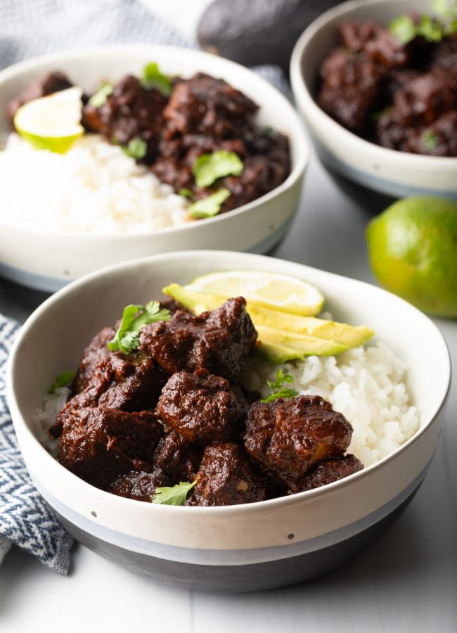 side view red chile pork carne adovada in a bowl with white rice, avocado, lime and cilantro