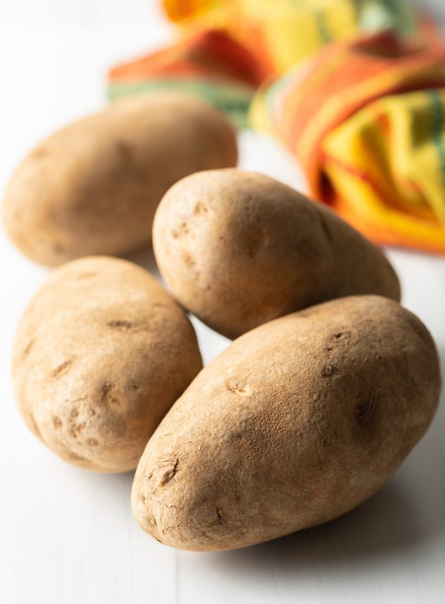 whole russet potatoes on a white background