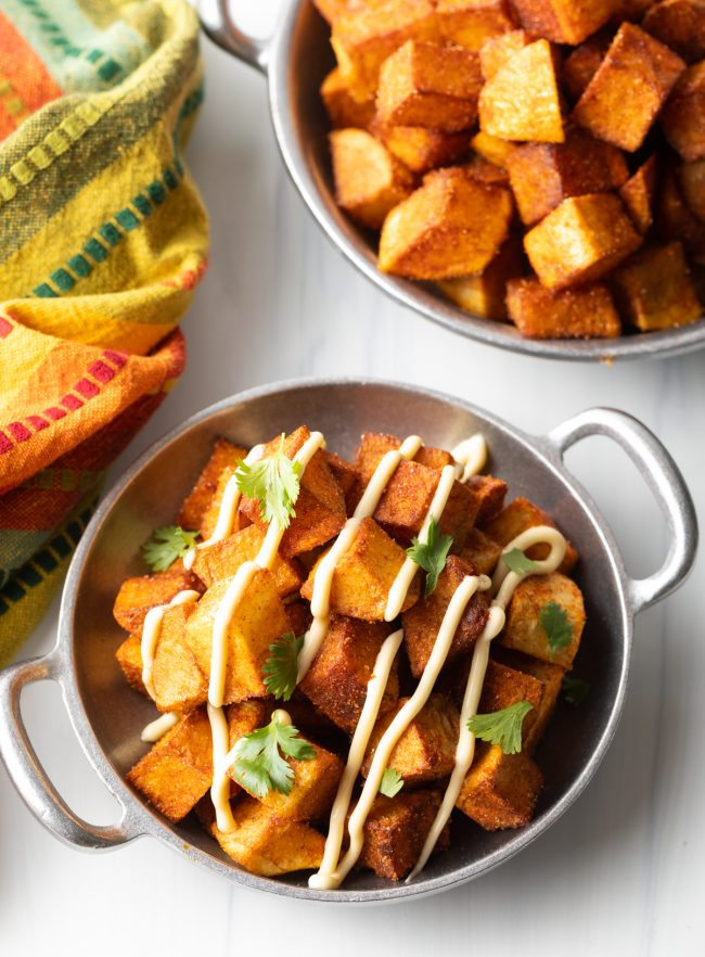overhead top view two bowl with Mexican fried potatoes with aioli and chopped cilantro | final view of competed patatas bravas recipe