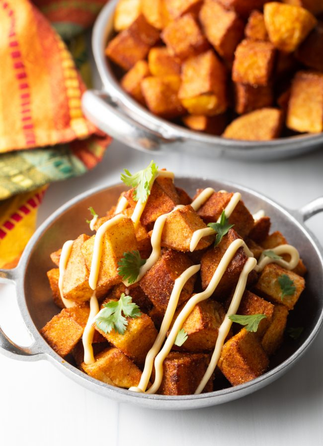bowl of crunchy patatas bravas in a silver bowl with aioli and cilantro on top