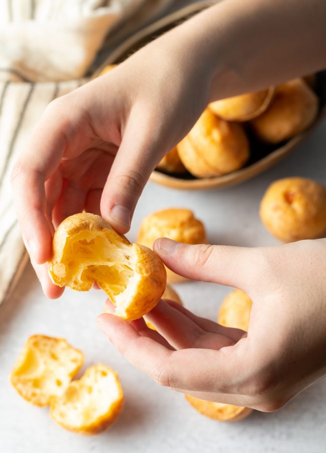 hands pulling apart a cheesy baked puff