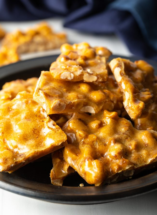 close view of pieces of peanut brittle stacked on a black plate