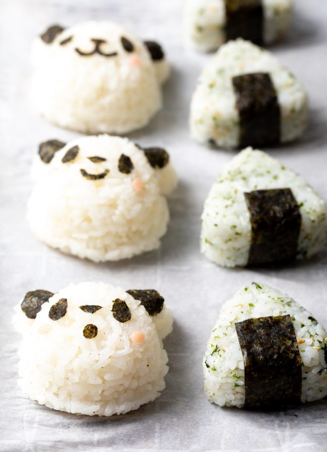 side view of panda japanese rice balls and triangle onigiri on parchment paper