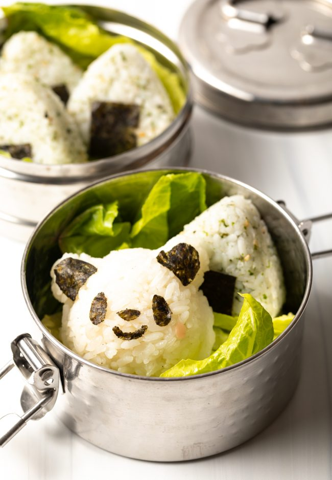 panda and triangle japanese rice balls with lettuce in a metal lunch tin