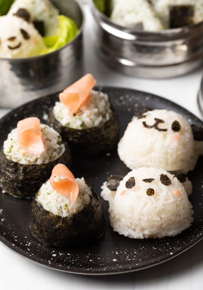 side view of plate with panda rice balls and rolled balls wrapped in nori and topped with sushi ginger