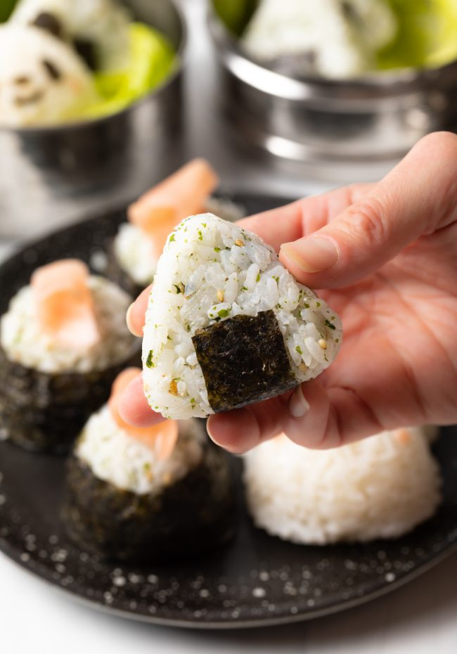hand holding triangle shaped onigiri with nori