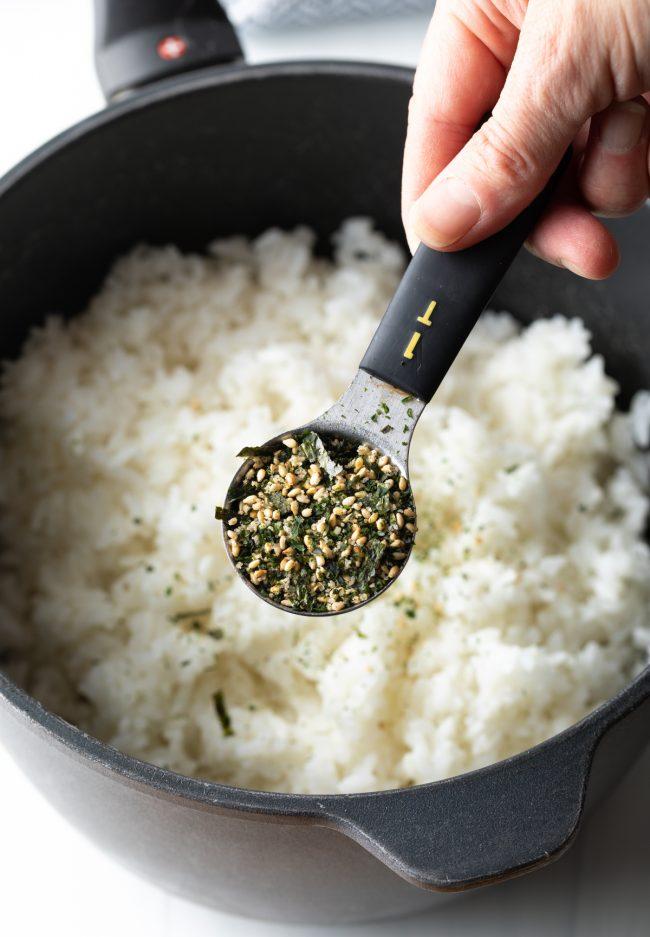 adding furikake mix to the cooked rice