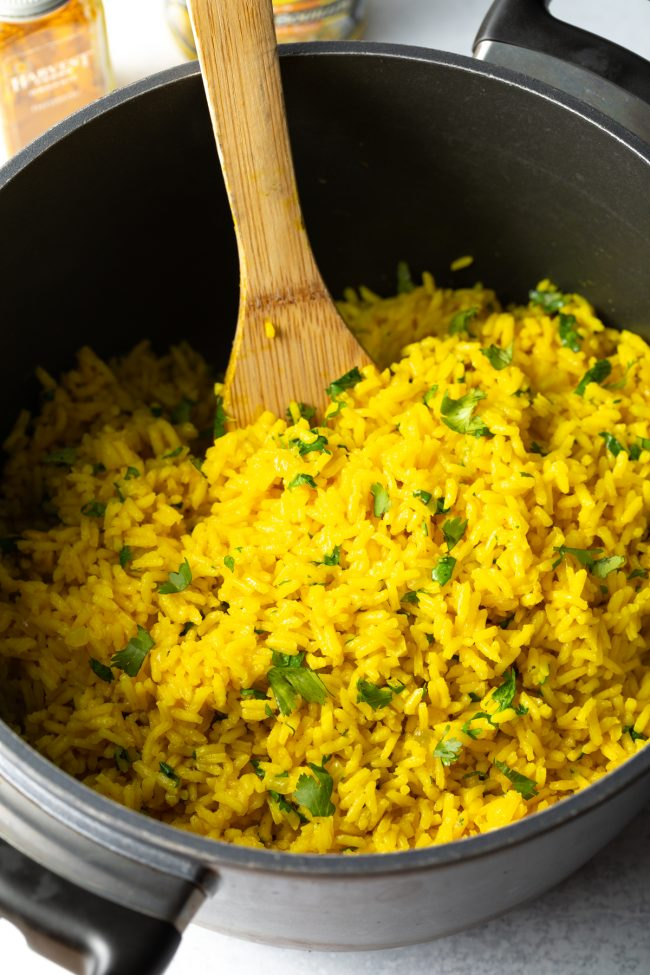 cooking pot with finished yellow rice, arroz amarillo being stirred with a spoon