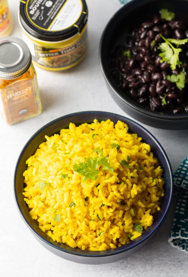 overhead view of spanish yellow rice in a bowl and bowl of cooked black beans