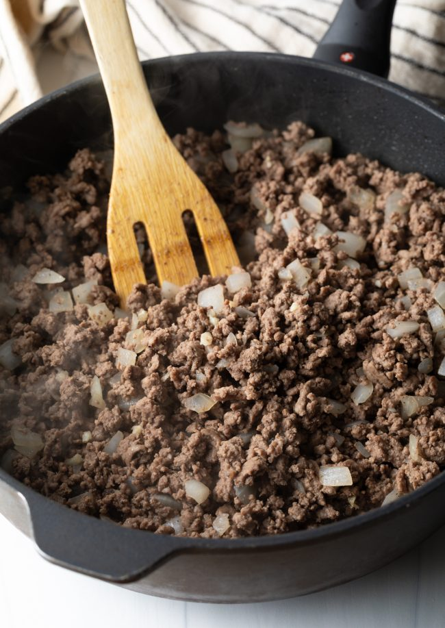 skillet with cooked ground beef and onions