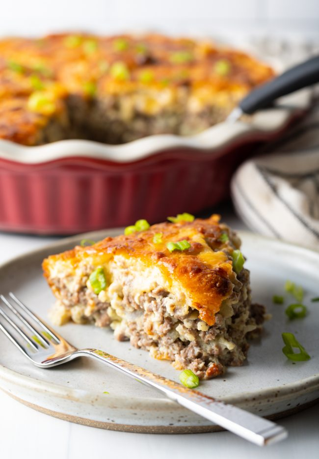 side view of a slice of savory pie loaded with ground beef and topped with a layer of cheese and bisquick topping