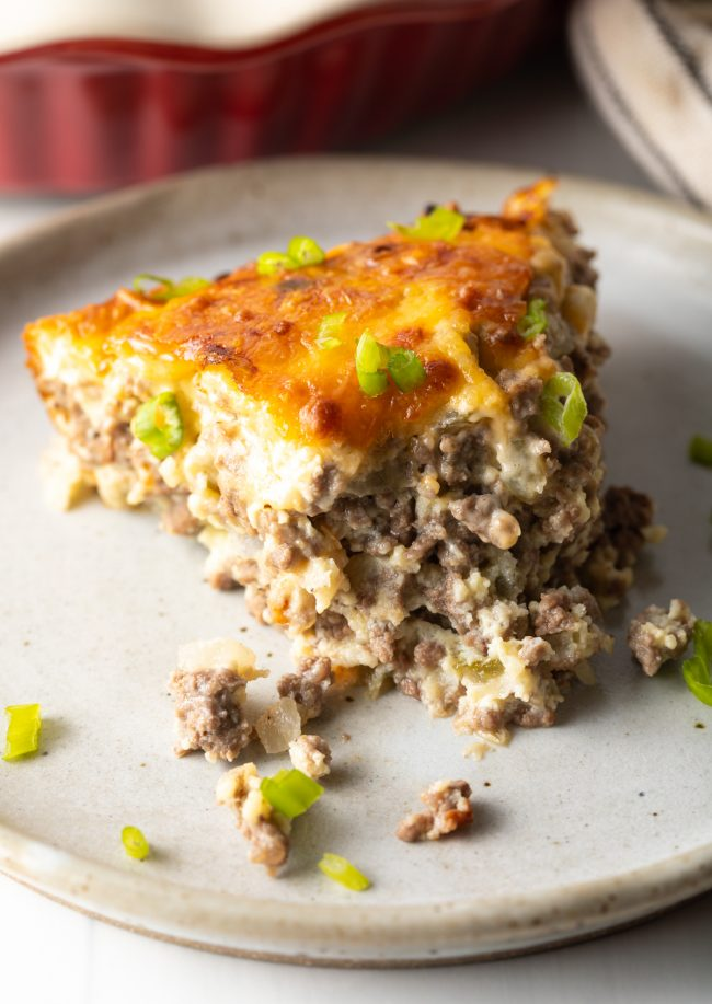 close up view slice of cheeseburger pie with bite take out, showing the ground beef and cheesiness with scallions and a Bisquick topping