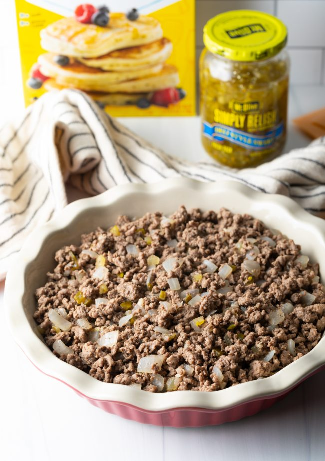 pie pan with layer of cooked ground beef, onions, pickle relish and mustard