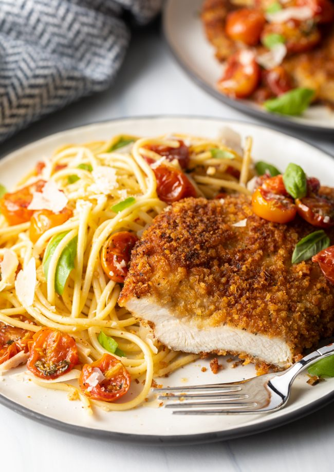 final shot showing Italian chicken cutlet cut into with a fork on a plate, spaghetti and cherry tomato sauce on the side