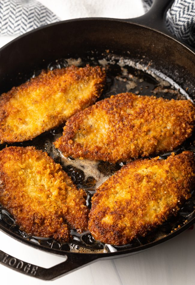 large cast iron pan frying crispy chicken cutlets with Italian marinade and seasoning