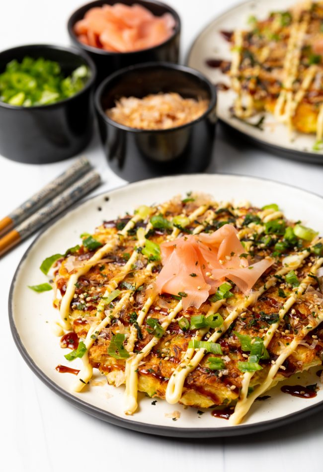 side view of finished Japanese cabbage pancake with loaded with scallions, ginger, kewpie mayo, and Okonomiyaki sauce