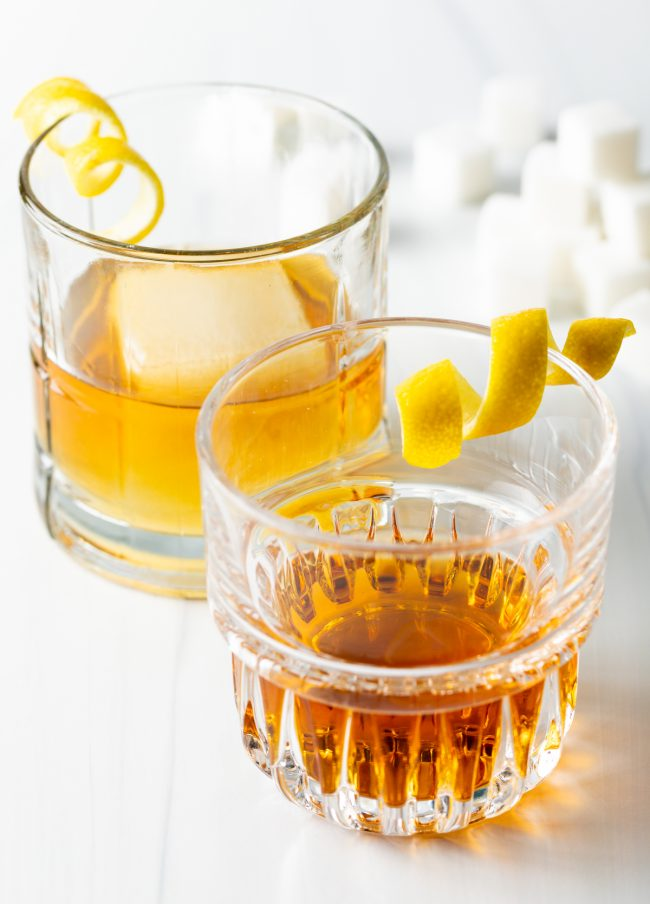 two sazerac cocktails one in front of the other with twists of lemon