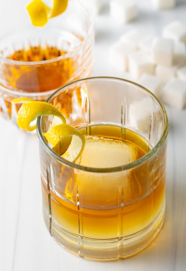 close up view of drink made with Sazerac rye whisky, bitters, sugar, and garnished with a twist of lemon