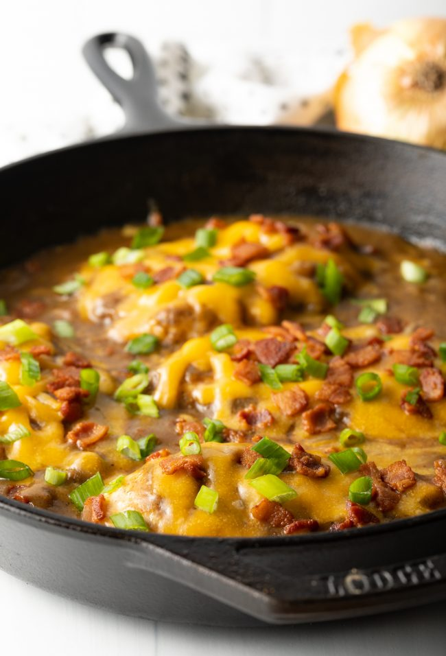 finished smothered chicken breast recipe view with cheese and bacon and scallions