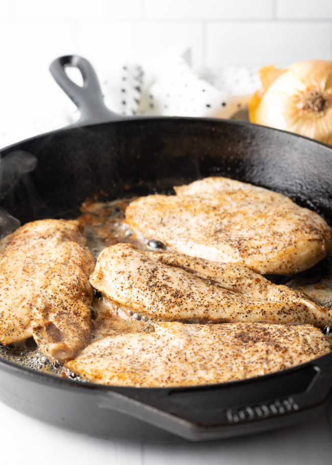 skillet with seasoned chicken breasts cooking in grease