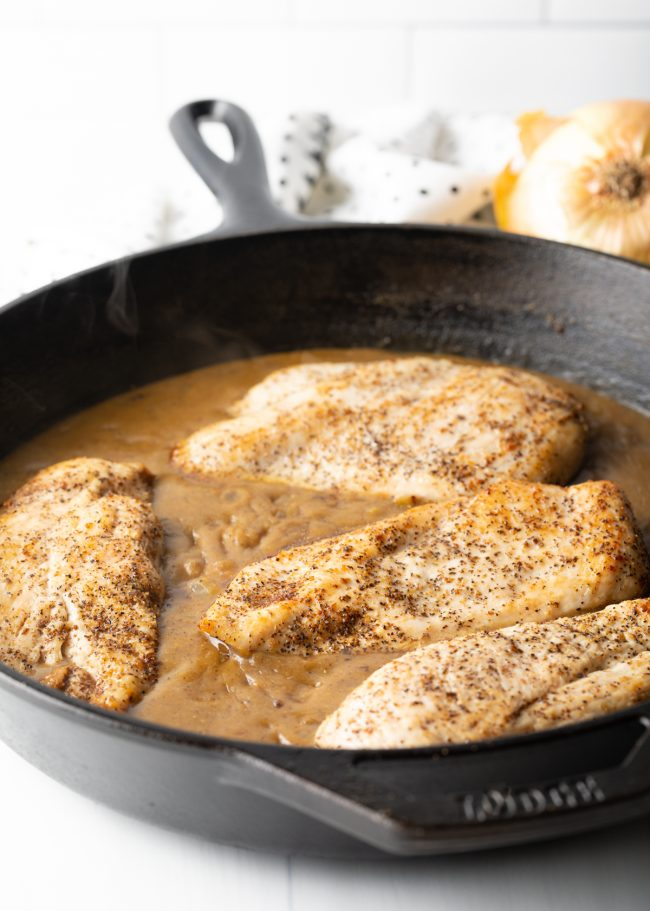 chicken breasts with gravy in a heavy skillet