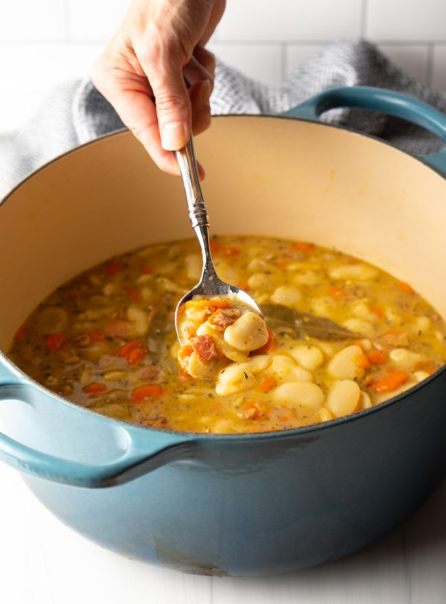 hand spooning butter beans with bacon from a large pot