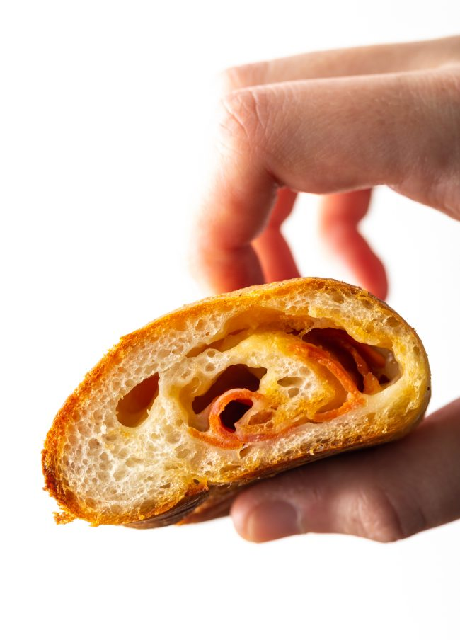 close up view of inside of pepperoni roll held by a hand