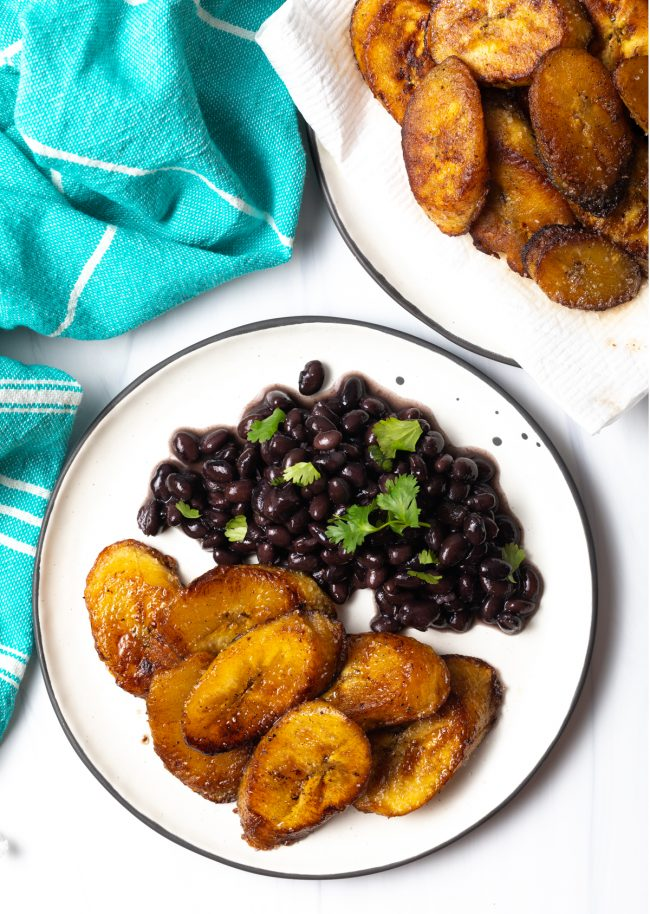 overhead view of sweet fried plantains on a plate with black beans and cilantro